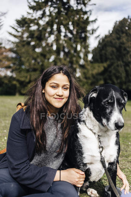 Mulher sentada com cão mestiço — Fotografia de Stock