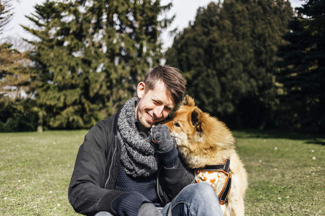 Man playing with Eurasier in park — Stock Photo