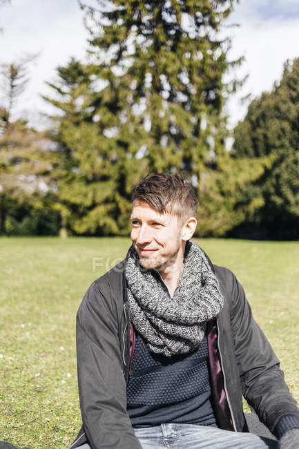 Young man sitting in park — Stock Photo