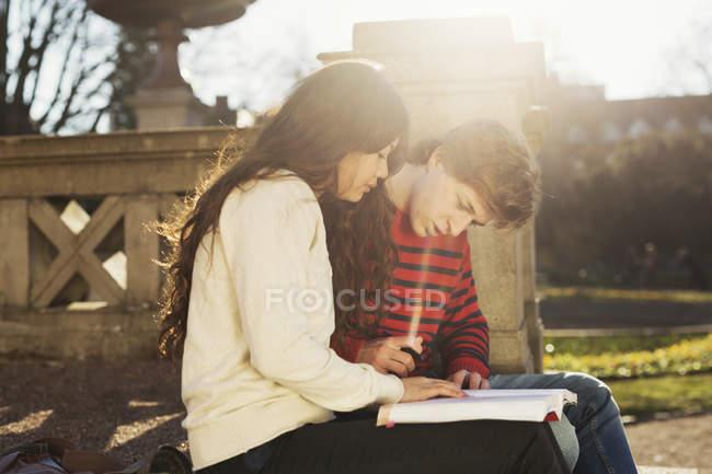 Adolescent garçon et fille lecture livre — Photo de stock