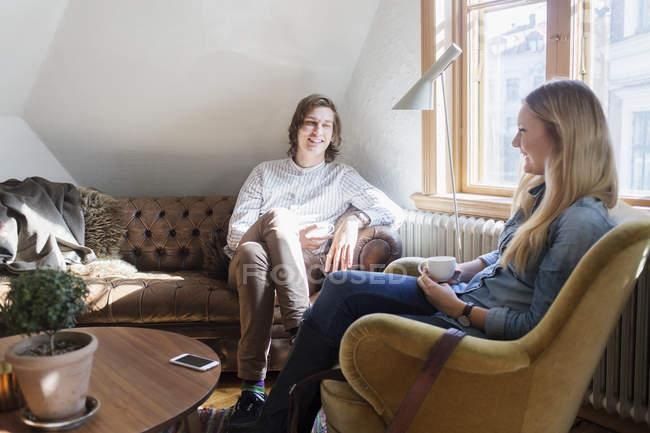 Amici felici comunicare in caffetteria — Foto stock