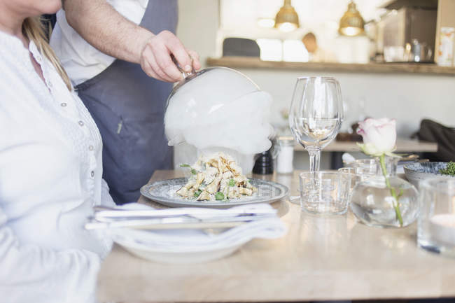 Waiter lifting cloche from dish — Stock Photo