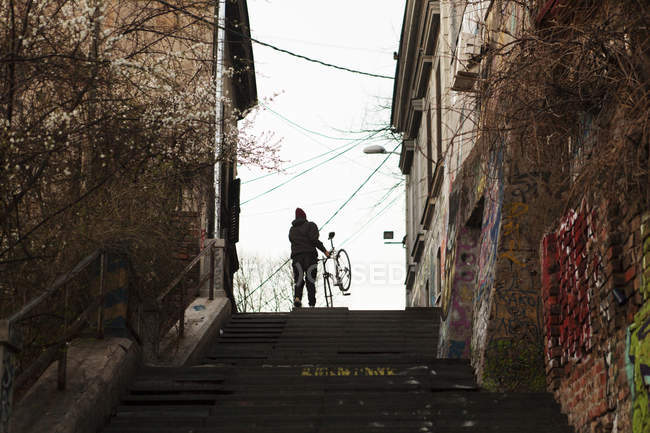 Person with bicycle moving up steps — Stock Photo