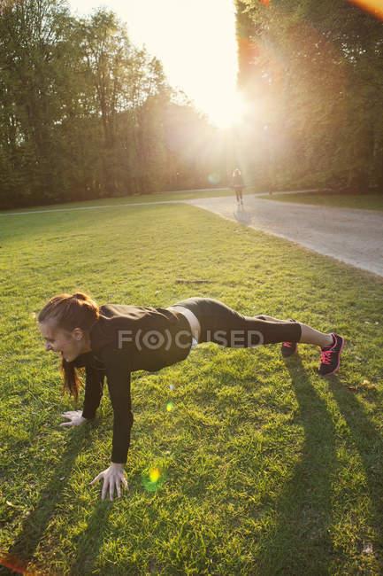 Young woman doing push-ups — Stock Photo