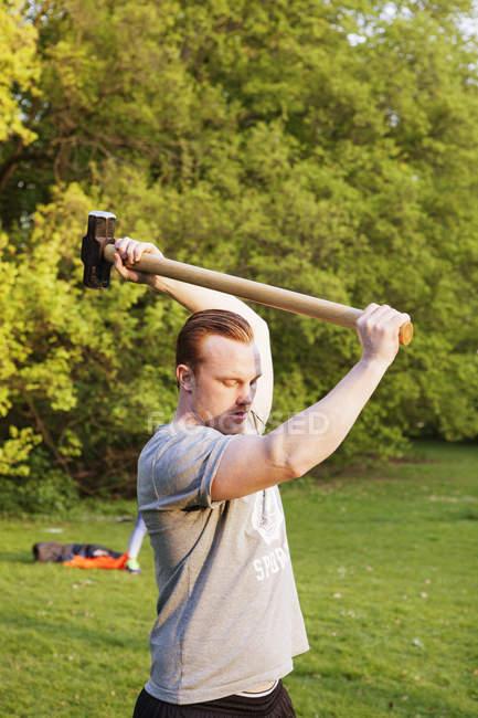 Jovem homem levantando martelo no parque — Fotografia de Stock