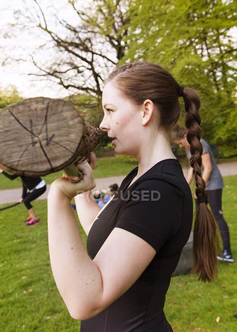 Mulher segurando log e exercício no parque — Fotografia de Stock
