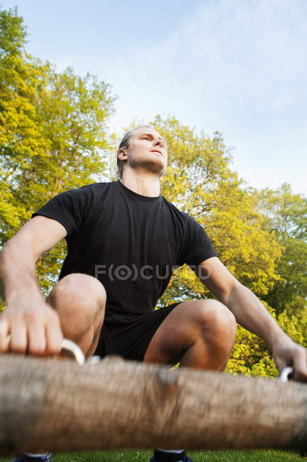 Young man exercising with log — Stock Photo