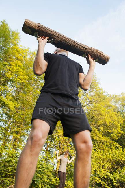 Jovem homem levantamento log no parque — Fotografia de Stock