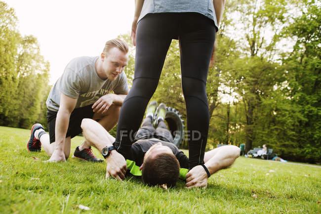 Amigos assistindo o homem no exercício — Fotografia de Stock