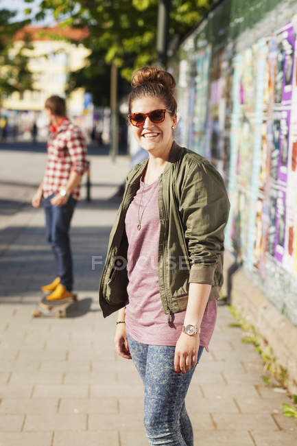 Happy woman standing on sidewalk — Stock Photo