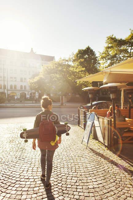 Женщина со скейтбордом и рюкзаком — стоковое фото