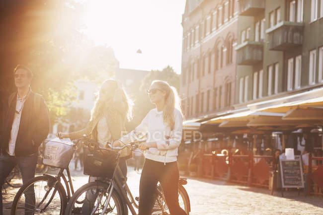 Amigos com bicicletas andando na rua — Fotografia de Stock