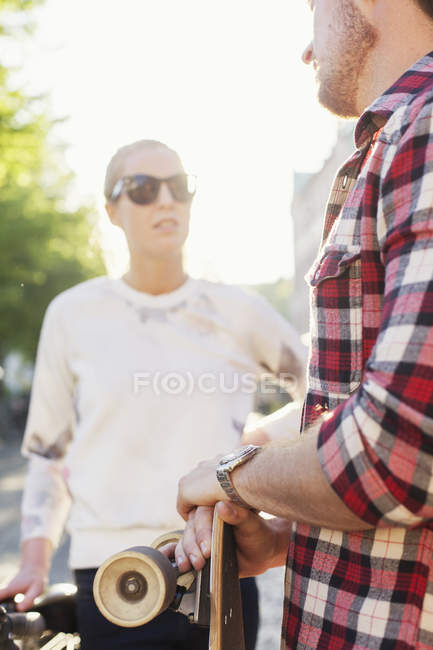 Friends with skateboard standing on street — Stock Photo