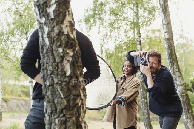 Друзья, фотографирование человек, опираясь на дерево — стоковое фото