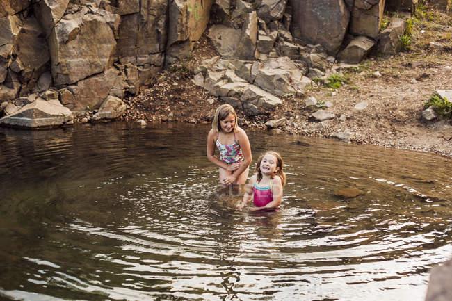 Playful girls enjoying in lake — Stock Photo