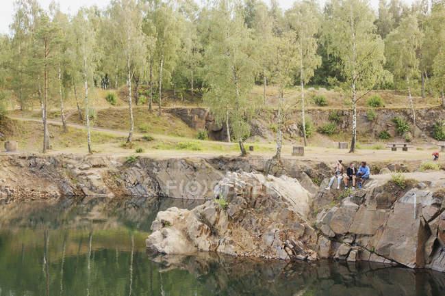 Amigos sentados en la roca por el lago - foto de stock