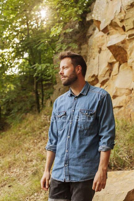 Uomo in piedi contro la roccia nella foresta — Foto stock