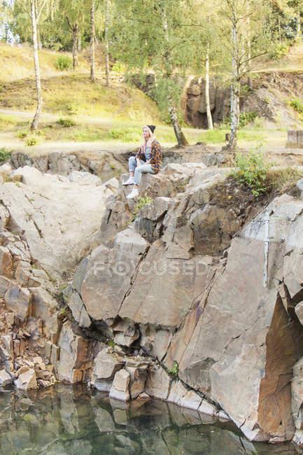 Молодая женщина, сидящая на скале — стоковое фото