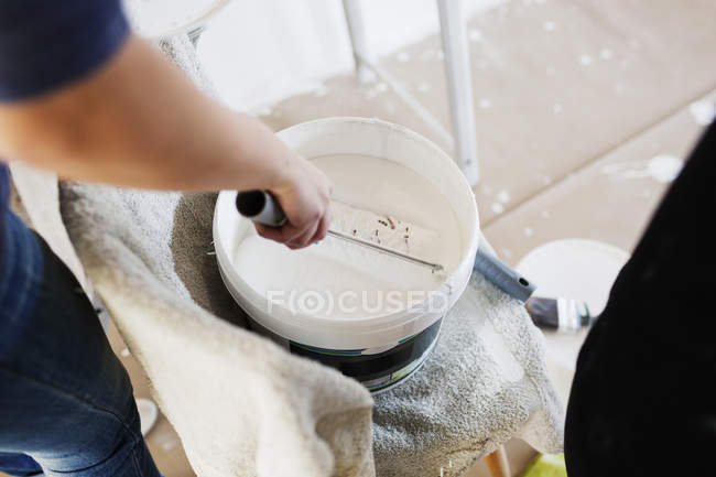 Human hand dipping paint roller — Stock Photo