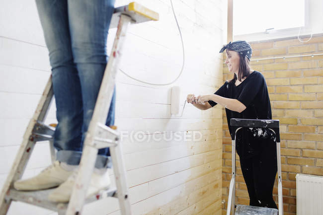 Woman painting wooden wall — Stock Photo
