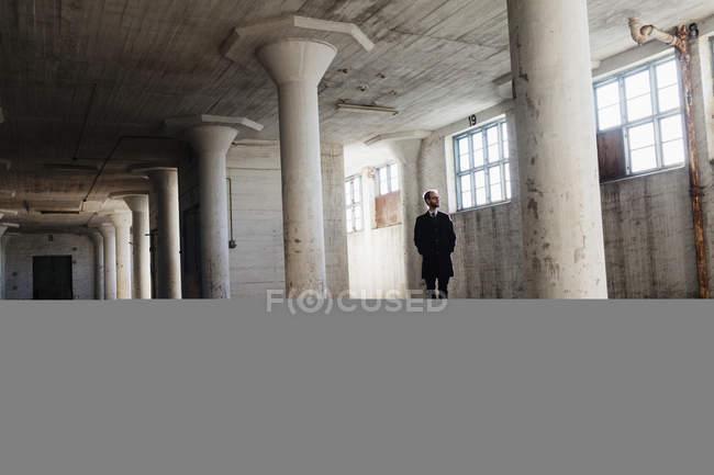 Solitario hombre de negocios en edificio abandonado - foto de stock
