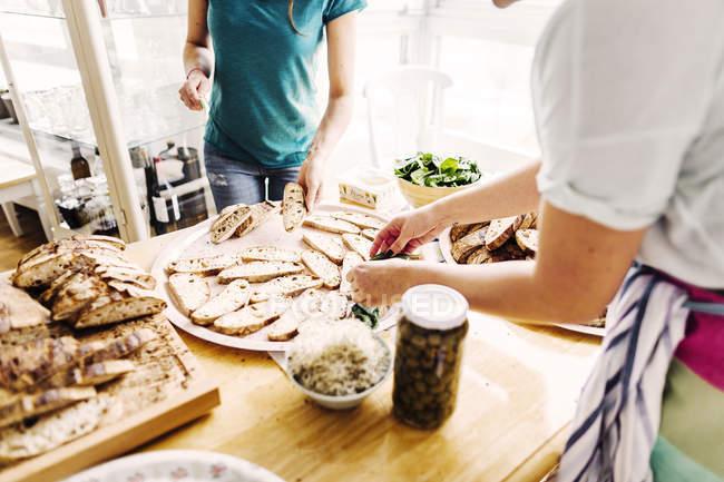 Женщины готовят сэндвичи с открытым лицом — стоковое фото
