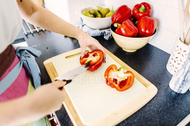 Woman cutting red bell pepper — Stock Photo