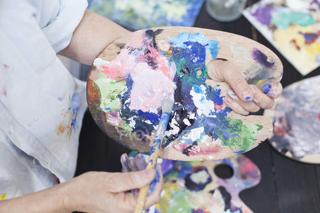 Senior woman using palette — Stock Photo