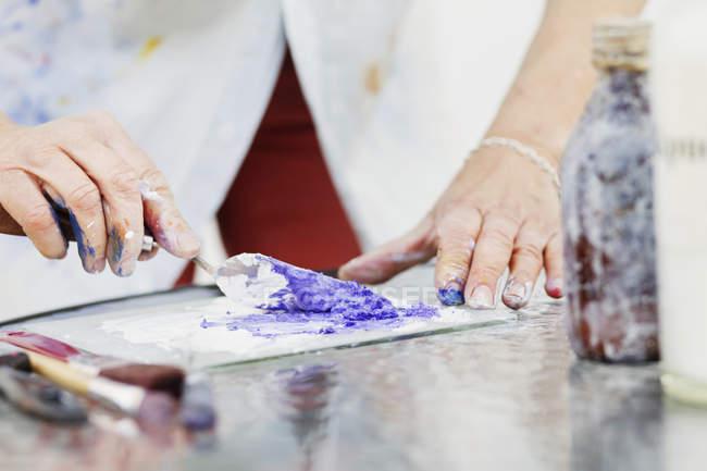 Female artist mixing paint — Stock Photo