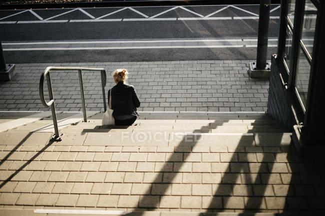 Mulher sentada em degraus — Fotografia de Stock