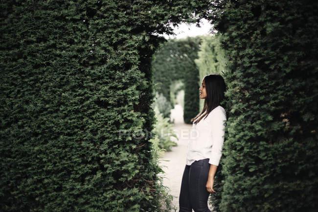 Mulher se apoiando em arbustos — Fotografia de Stock