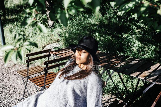 Женщина сидит на стуле в парке — стоковое фото