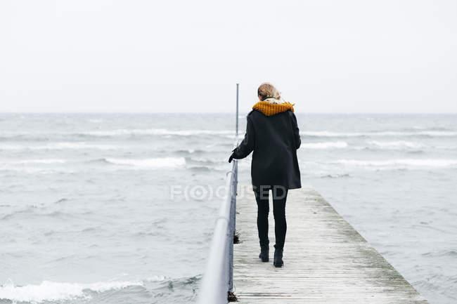 Mulher andando no cais sobre mar — Fotografia de Stock