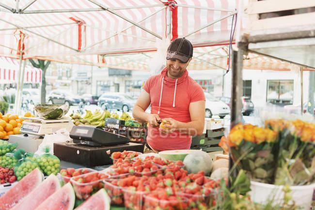 Venditore taglio frutta in bancarella nel mercato — Foto stock