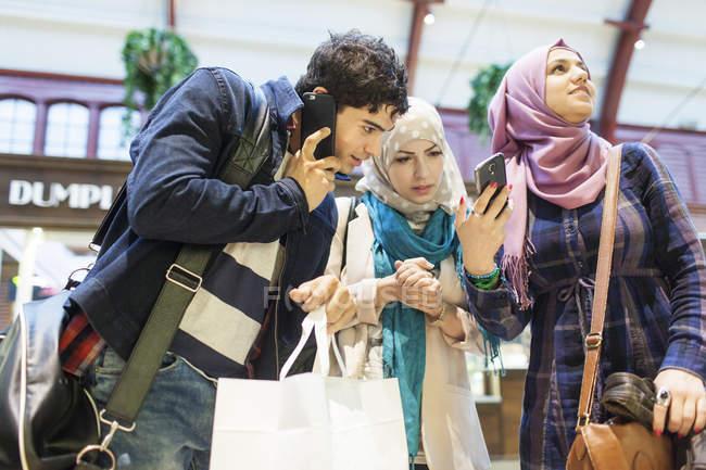 Jovens amigos usando telefones inteligentes — Fotografia de Stock