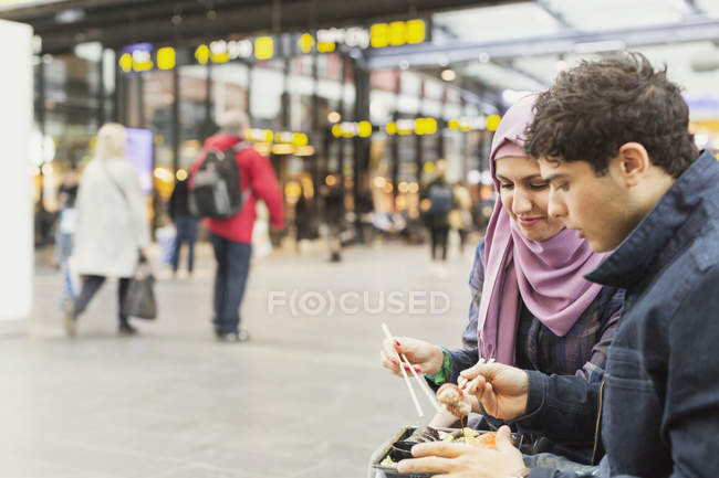 Friends having sushi at railroad station — Stock Photo