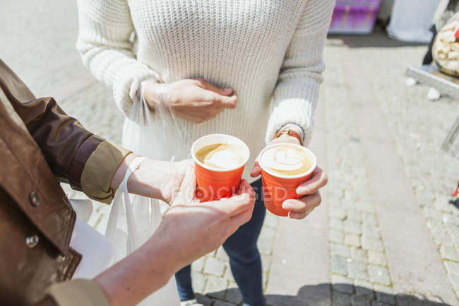 Friends holding coffee cups — Stock Photo
