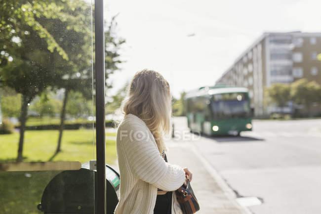 Junge Frau an Bushaltestelle — Stockfoto