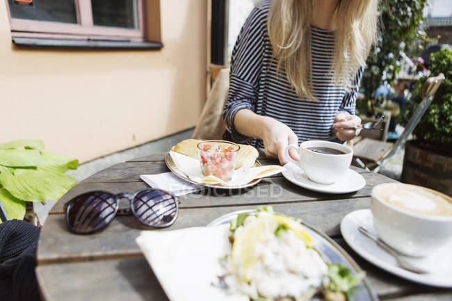 Woman having food at sidewalk cafe — Stock Photo