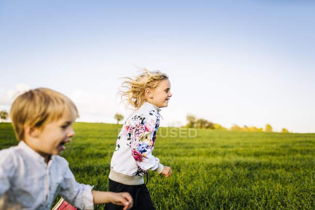 Cheerful siblings running — Stock Photo