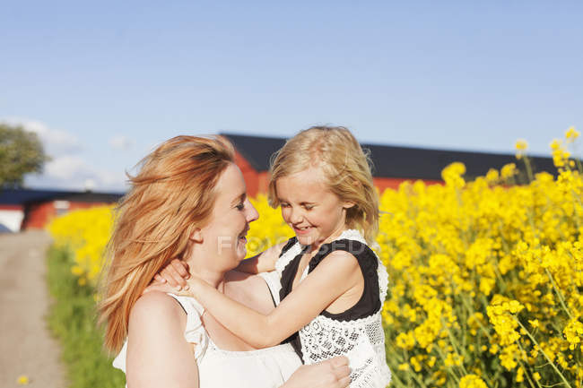 Happy woman carrying daughter — Stock Photo