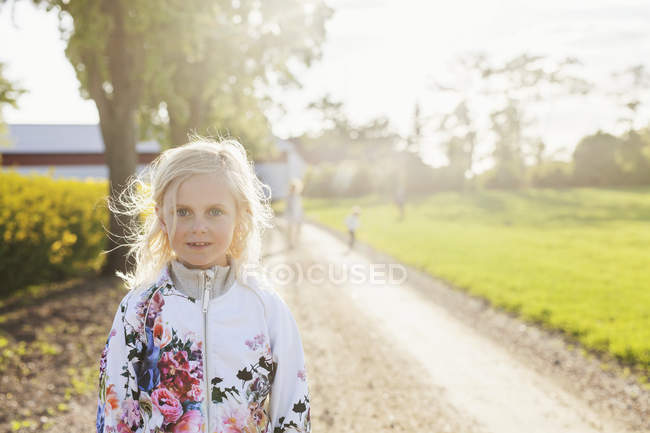 Smiling girl standing on dirt road — Stock Photo