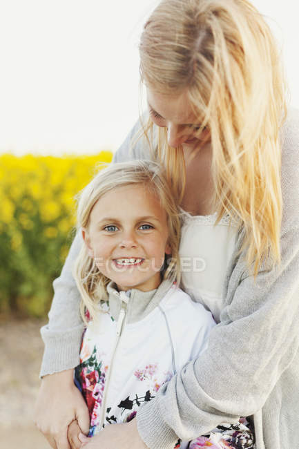 Happy girl standing with loving mother — Stock Photo