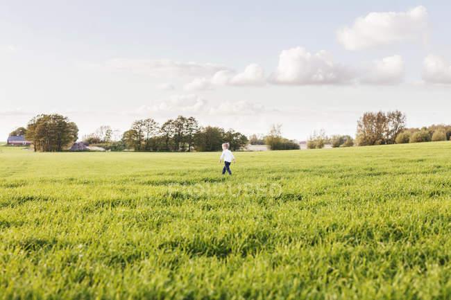 Boy walking on grassy field — Stock Photo