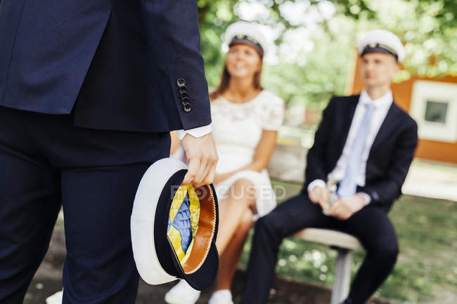 Graduate holding cap while friends sitting — Stock Photo
