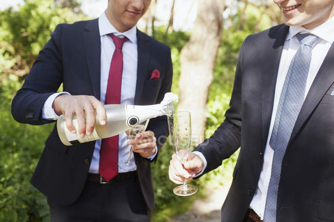 Male graduate pouring champagne — Stock Photo