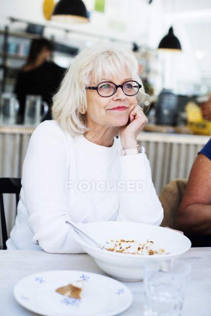 Senior femme assise dans le restaurant — Photo de stock