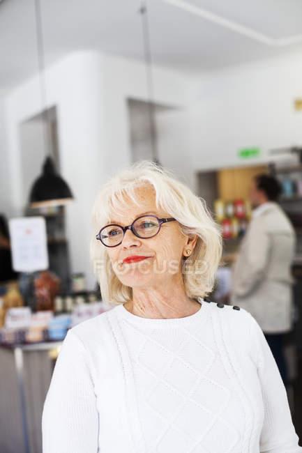 Senior femme souriant au restaurant — Photo de stock