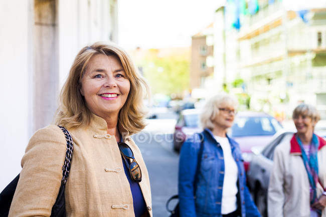 Senior woman standing with friends — Stock Photo