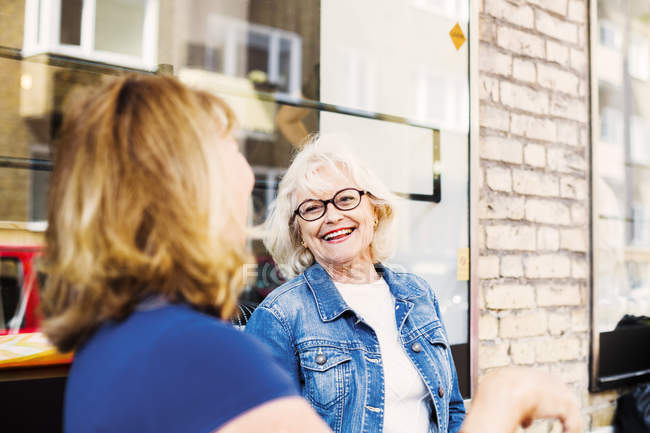 Senior women laughing at cafe — Stock Photo
